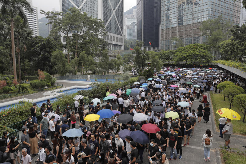 Hundreds of accountants march at Chater Garden in Hong Kong, Friday, Aug. 23, 2019. Protesters demand the government to fully withdraw the extradition bill and set up an independent committee to investigate the use of force by the Hong Kong police. (AP Photo/Kin Cheung)