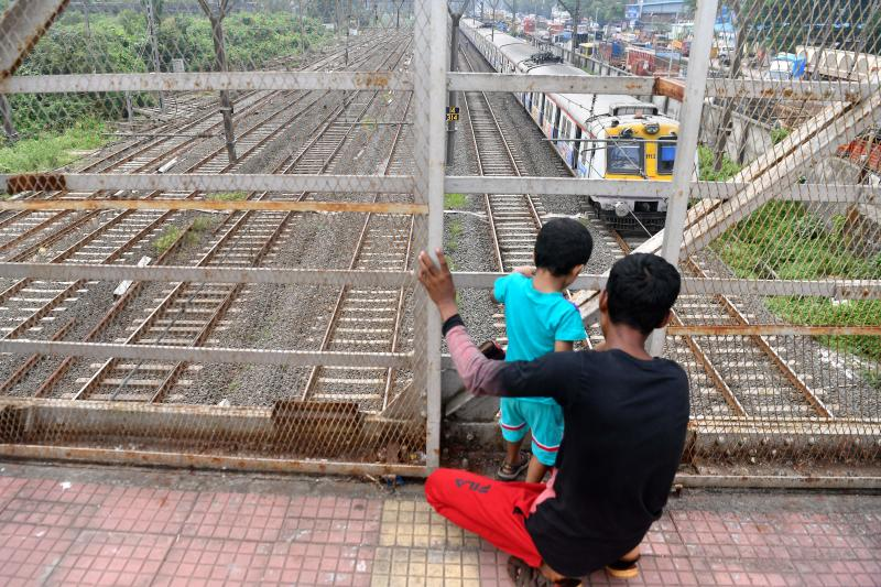 A man and a child look at a local train stranded due to a major power cut in several areas after grid failure in Mumbai on October 12, 2020. (Photo by INDRANIL MUKHERJEE / AFP) (Photo by INDRANIL MUKHERJEE/AFP via Getty Images)