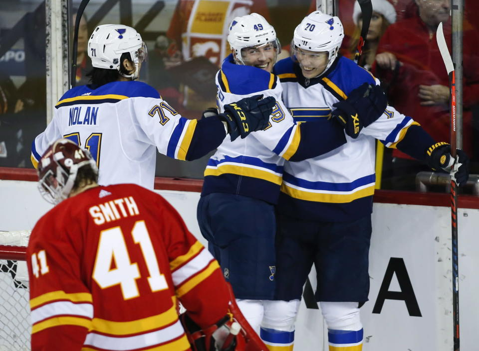 St. Louis Blues' Oskar Sundqvist, right, of Sweden, celebrates his goal with teammates Ivan Barbashev, center, of Russia, and Jordan Nolan, left, as Calgary Flames goalie Mike Smith looks away during the third period of an NHL hockey game Saturday, Dec. 22, 2018, in Calgary, Alberta. (Jeff McIntosh/The Canadian Press via AP)