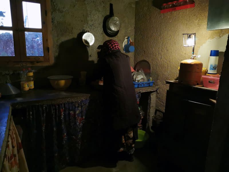 Mohammed Akki's wife works in the kitchen of their home that has no electricity and is lit by a gas lamp in the community of Ait Hammou Ouhmad on the edge of Azrou