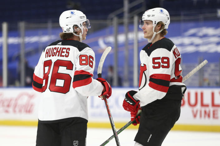 New Jersey Devils forward Jack Hughes (86) celebrates his goal with forward Janne Kuokkanen (59) during the first period of the team's NHL hockey game against the Buffalo Sabres, Thursday, April 8, 2021, in Buffalo, N.Y. (AP Photo/Jeffrey T. Barnes)