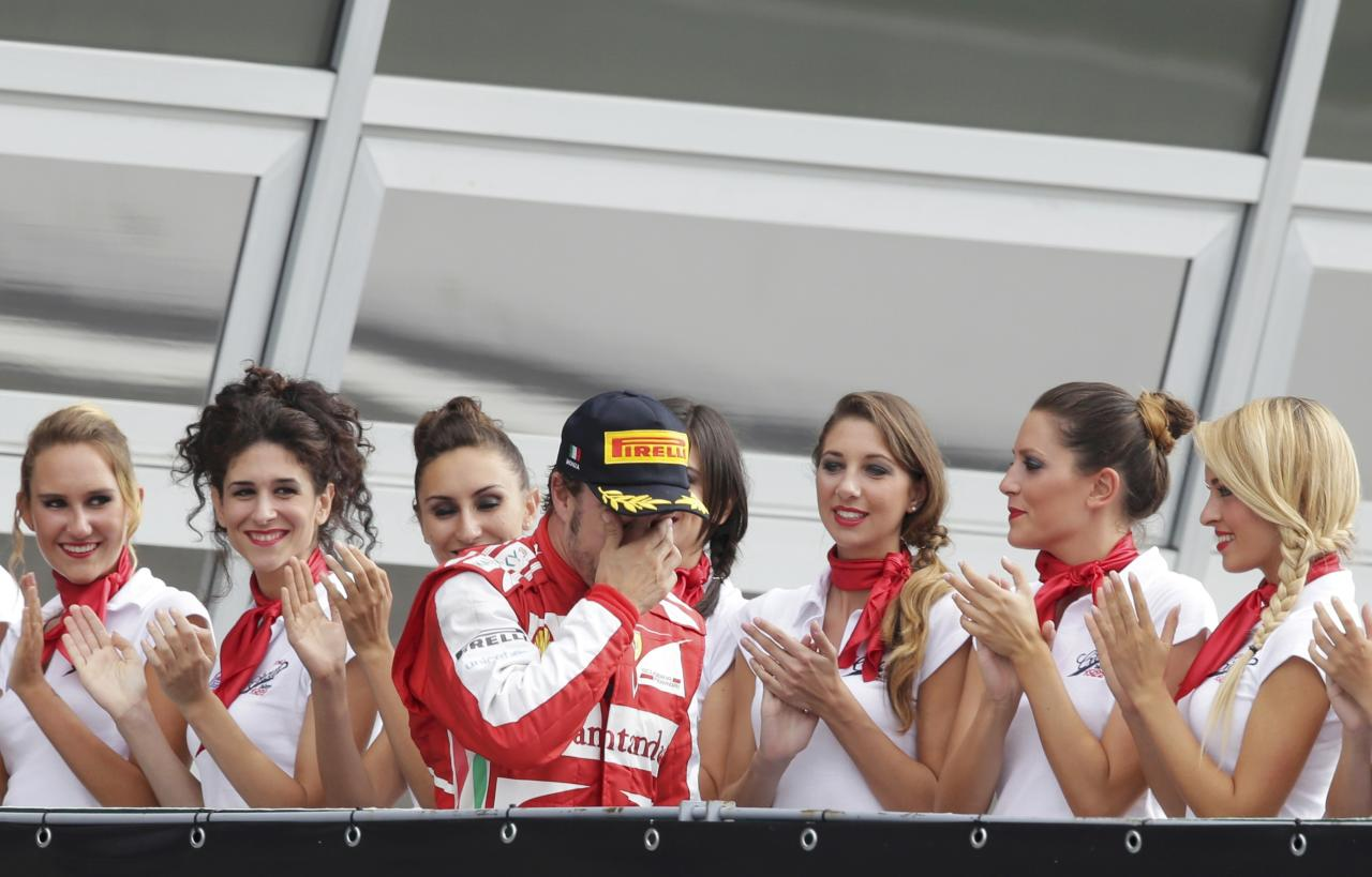Ferrari Formula One driver Fernando Alonso of Spain arrives on the podium after placing second in the Italian F1 Grand Prix at the Monza circuit September 8, 2013. REUTERS/Max Rossi (ITALY - Tags: SPORT MOTORSPORT F1)