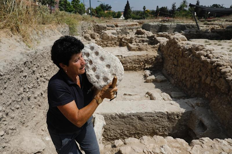 Israel Antiquities Authority archaeologist Alla Nagorsky carries a 1,600-year-old Mancala game from the Byzantine time found during a large excavation in the central Israeli town of Gedera (AFP Photo/MENAHEM KAHANA)