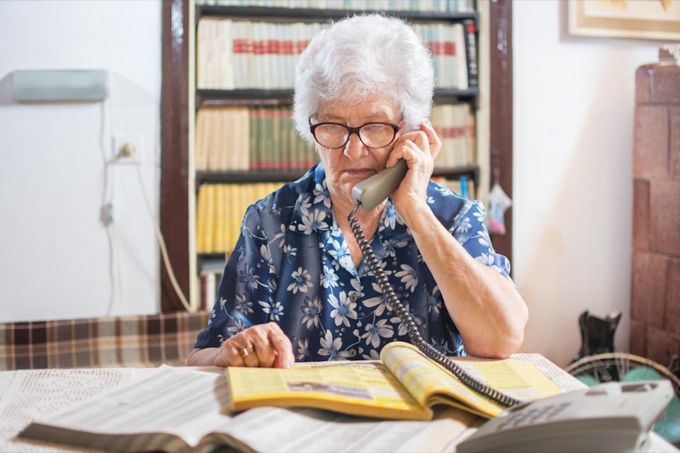 senior woman calling from a yellow phone book
