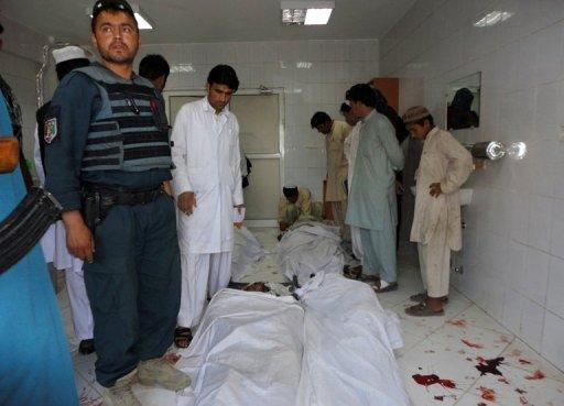 Afghan policeman and civilians gather at a hospital morgue holding the bodies of suicide bombing victims in Khost