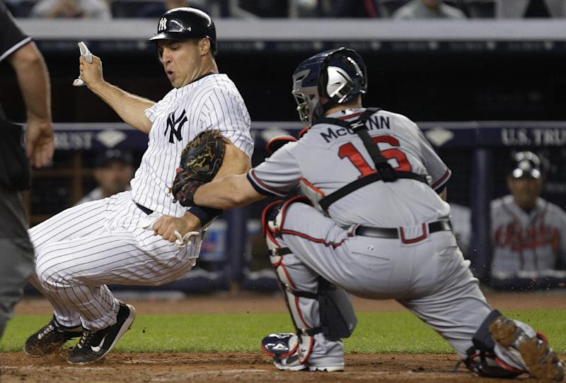 Atlanta Braves catcher Brian McCann (16) tags out New York Yankees' Mark Teixeira during the fifth inning of a baseball game at Yankee Stadium in New York, Tuesday, June 19, 2012. (AP Photo/Kathy Willens)