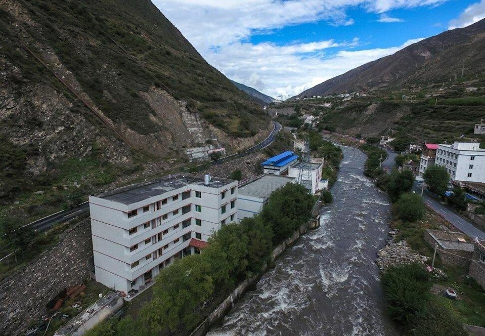 """A bitcoin """"mine"""" with a blue tin roof sits next to a hydroelectric power plant in Ngawa (Aba) Tibetan and Qiang Autonomous Prefecture, Sichuan province, on September 27, 2016. Beijing is cracking down on energy-intensive mining activities, but Sichuan could let the booming industry take advantage of excess hydropower over the summer. Photo: EPA"""