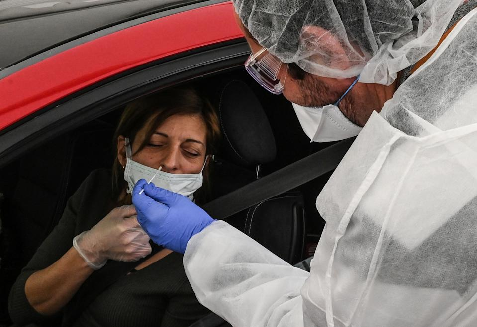 "A laboratory technician takes a sample from a health personnel at a ""Drive"" center in Montpellier, in the south of France, on March 27, 2020, during the eleventh day of a blockade aimed at slowing down the spread of the novel coronavirus, COVID-19, in France. (Photo by Pascal GUYOT / AFP) (Photo by PASCAL GUYOT/AFP via Getty Images)"
