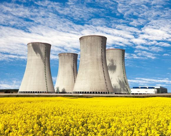 Four nuclear reactors on a yellow field against the blue sky.