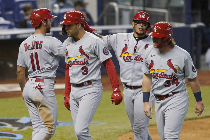 St. Louis Cardinals' John Nogowski (34), Yadier Molina (4) and Paul DeJong (11) congratulate Dylan Carlson (3) after Carlson hit a grand slam in the ninth inning of a baseball game against the Miami Marlins, Wednesday, April 7, 2021, in Miami. The Cardinals defeated the Marlins 7-0. (AP Photo/Marta Lavandier)