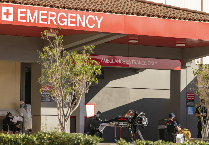 """An unidentified patient receives oxygen on a stretcher, while Los Angeles Fire Department Paramedics monitor him outside the Emergency entrance, waiting for admission at the CHA Hollywood Presbyterian Medical Center in Los Angeles Friday, Dec. 18, 2020. Increasingly desperate California hospitals are being """"crushed"""" by soaring coronavirus infections, with one Los Angeles emergency doctor predicting that rationing of care is imminent. (AP Photo/Damian Dovarganes)"""