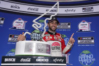 Chase Elliott, left, poses with the trophy in Victory Lane after winning a NASCAR Cup Series auto race at Circuit of the Americas in Austin, Texas, Sunday, May 23, 2021. (AP Photo/Chuck Burton)