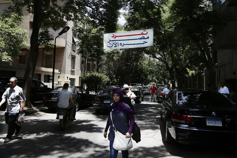 """FILE - In this file photo taken Wednesday, June 26, 2013, Egyptians walk below a banner of Tamarod, or """"rebel,"""" with Arabic that reads, """"Tamarod, Egypt now is free,"""" a campaign calling for the ouster of Egyptian President Mohammed Morsi, in Cairo, Egypt. No matter what happens in anti-Morsi protest planned for June 30, 2013, organizers of the petition campaign that led to it say they have created a grassroots network of new activists they hope will remain a voice for the public. (AP Photo/Hassan Ammar, File)"""
