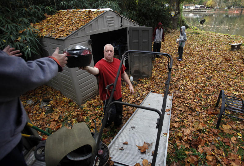 Mike Coyle hands his sister Stephanie Colye an item taken from a shed as they load up belongings on River Road along the Schuylkill River in Philadelphia Sunday, Oct. 28, 2012. Tens of millions of people in the eastern third of the U.S. in the path of a massive freak storm had braced Sunday for the first raindrops that were expected later in the day, to be followed over the next few days by sheets of rain, high winds and even heavy snow. (AP Photo/Jacqueline Larma)