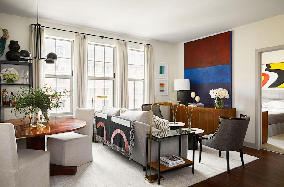 """Risdon's aptitude for mixing highs and lows shines in the open living-dining area of the designer's home. Risdon says that his """"splurge"""" was custom window treatments, fabricated by Essence Interiors in Fairfax, Virginia. An area rug, sourced locally from Carpet Palace, helps to tie the room together. The side tables, initially purchased on Wayfair for a client project, were reconfigured by Risdon to incorporate extra shelving and an antique mirror top."""
