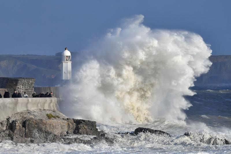 People gather to watch huge waves crash against the harbour wall at Porthcawl, Wales.