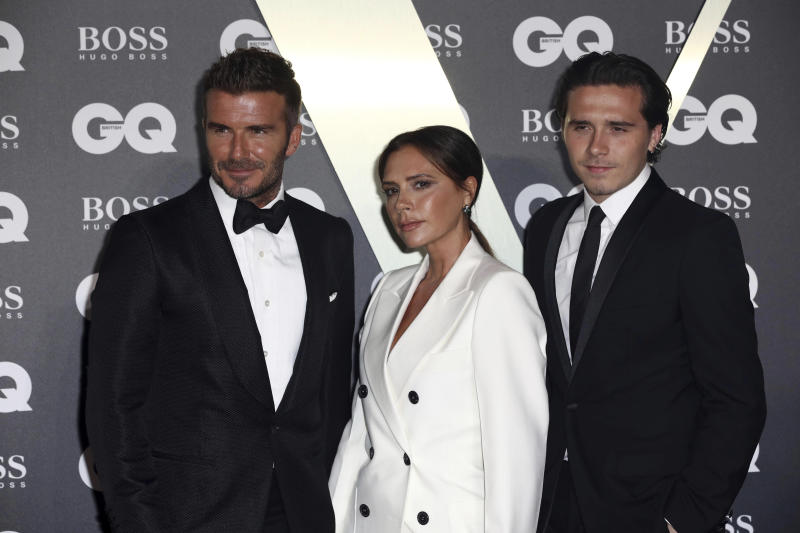 Footballer David Beckham, left, his wife Victoria Beckham, and their son Brooklyn Beckham, pose for photographers on arrival at the GQ Men of the year Awards in central London on Tuesday, Sept. 3, 2019. (Photo by Grant Pollard/Invision/AP)