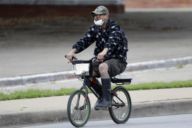 A man wearing a mask rides a bike through downtown Dallas, Tuesday, March 31, 2020. For most people, the coronavirus causes mild or moderate symptoms, such as fever and cough that clear up in two to three weeks. For some, especially older adults and people with existing health problems, it can cause more severe illness, including pneumonia and death. (AP Photo/Tony Gutierrez)