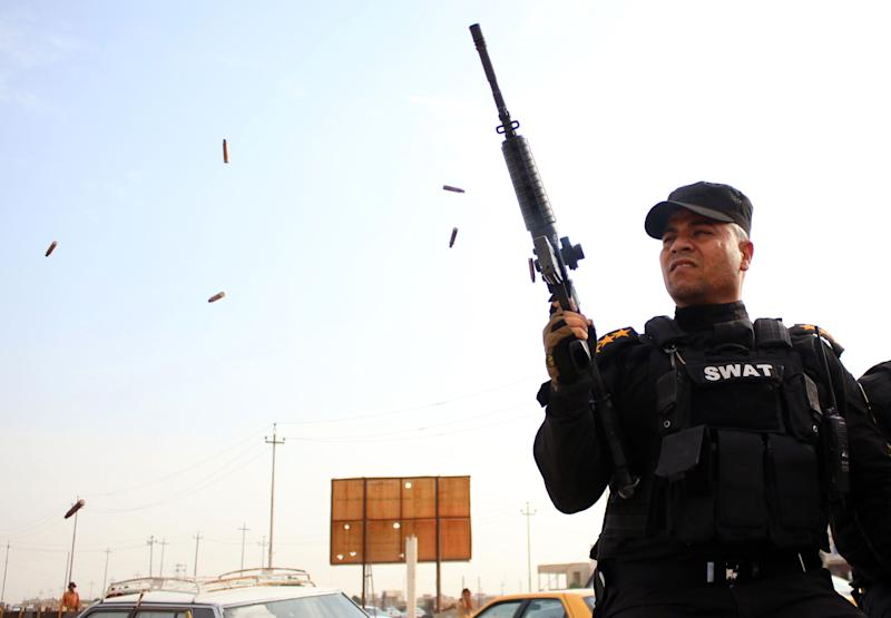 A member of Iraq's security forces fires ammunition in the air during the funeral procession of a member of parliament killed in a suicide blast, on October 15, 2014 in Baghdad (AFP Photo/Haidar Mohammed Ali)