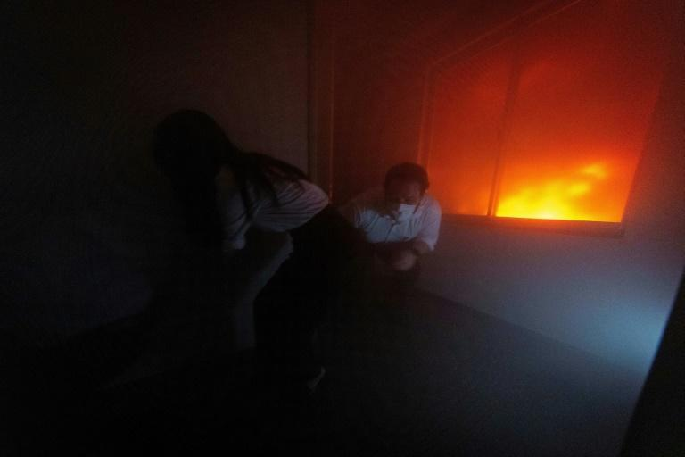 Visitors to the Ikebukuro Life Safety Learning Centre try to find an exit door during a fire simulation