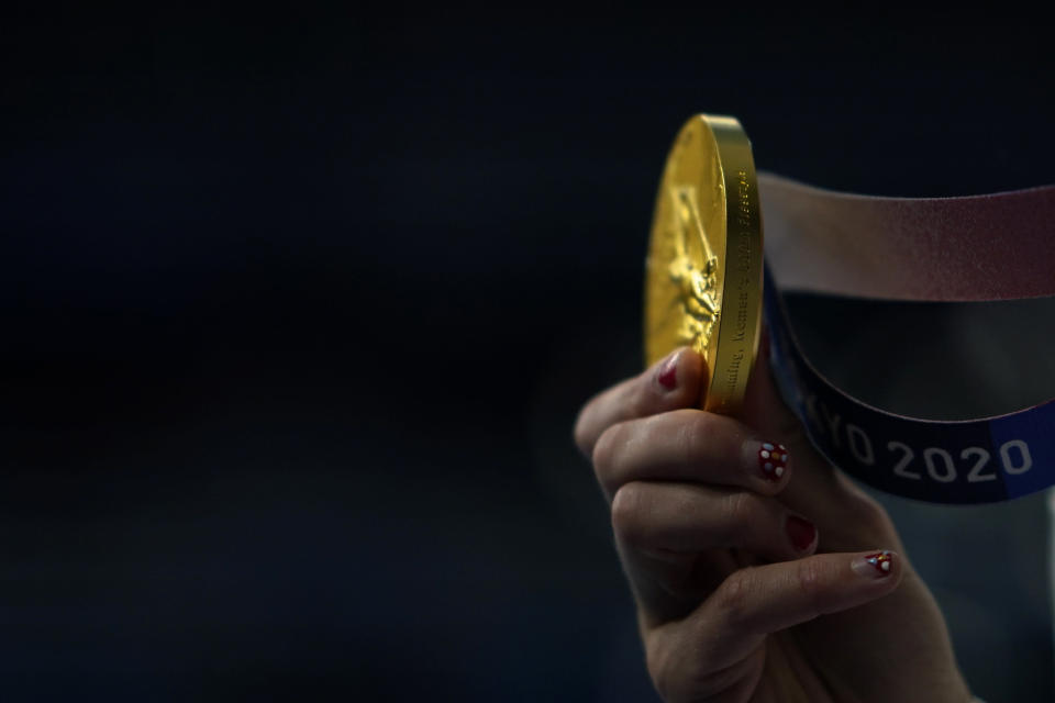 Kathleen Ledecky, of United States, shows her gold medal after winning the women's 800-meter freestyle final at the 2020 Summer Olympics, Saturday, July 31, 2021, in Tokyo, Japan. (AP Photo/David Goldman)