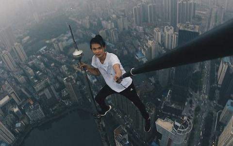 Wu performs another stunt, balancing on a narrow spike above a skyscraper - Credit: Wu Yongning/Weibo