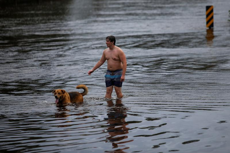 A man and his dog walk along a flooded street after the passage of tropical storm Florence in New Bern, North Carolina, U.S., September 16, 2018.