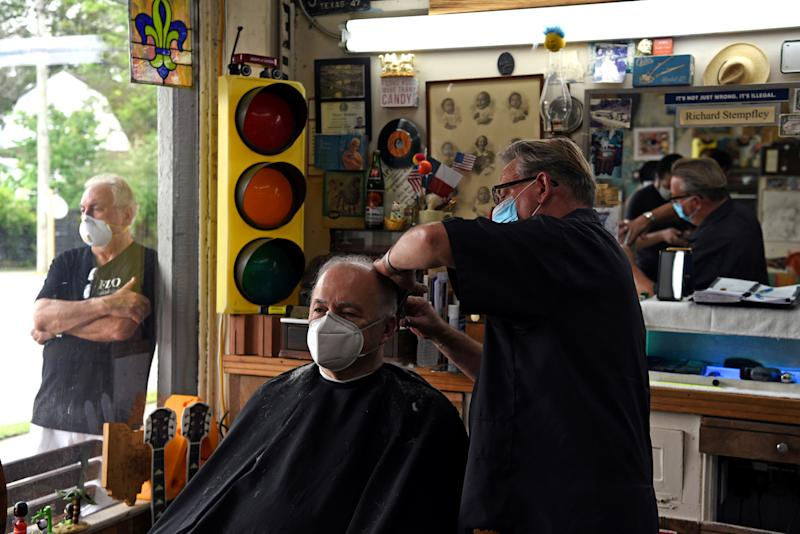 A man receives a haircut as social distancing guidelines to curb the spread of the coronavirus disease (COVID-19) are relaxed, at Doug's Barber Shop in Houston, Texas, U.S., May 8, 2020. REUTERS/Callaghan O'Hare TPX IMAGES OF THE DAY