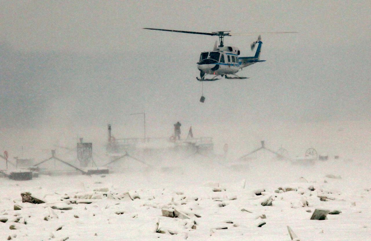A Serbian police helicopter delivers food to sailors stuck on stranded boats on the Danube river near Smederevo, Serbia, Monday, Feb. 13, 2012. In Serbia, heavy snow continues to fall as some 50,000 people remain stranded in snowbound remote areas, some without electricity. (AP Photo/Vladimir Gogic)