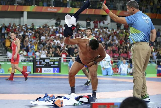 <p>The coach of Mandakhnaran Ganzorig (MGL) of Mongolia takes off his clothes as he protests after the match against Ikhtiyor Navruzov (UZB) of Uzbekistan. (Reuters) </p>