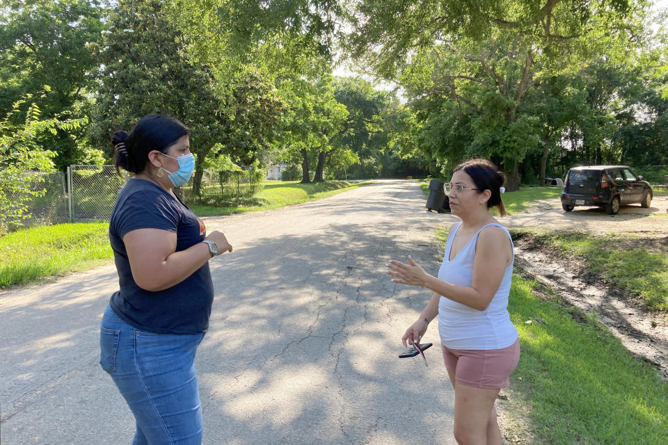 Shirley Ronquillo, a Houston area community activist, left, talks with Allen Field subdivision resident Dolores Mendoza about her neighborhood's history of flooding and efforts by officials to relocate residents through a buyout program on May 27, 2021. The recent decision by a Texas agency to not award the Houston area, which suffered the brunt of damage from Hurricane Harvey, any funding for flood mitigation has incensed residents like Ronquillo and Mendoza and in a rare show of bipartisanship, united local Democratic and Republican officials who condemned the decision. (AP Photo/Juan A. Lozano)