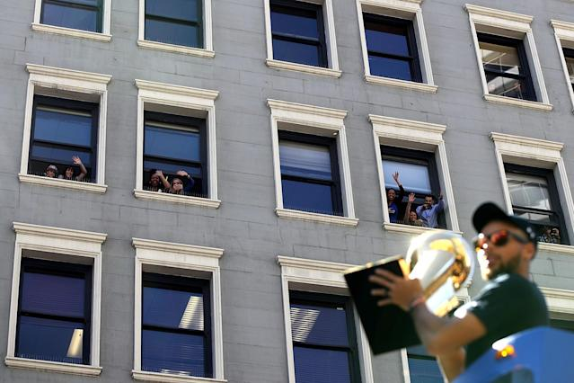 <p>Golden State Warriors fans wave from a building as Golden State Warriors Stephen Curry rides by on a float during the Warriors Victory Parade on June 15, 2017 in Oakland, California. An estimated crowd of over 1 million people came out to cheer on the Golden State Warriors during their victory parade after winning the 2017 NBA Championship. (Photo by Justin Sullivan/Getty Images) </p>