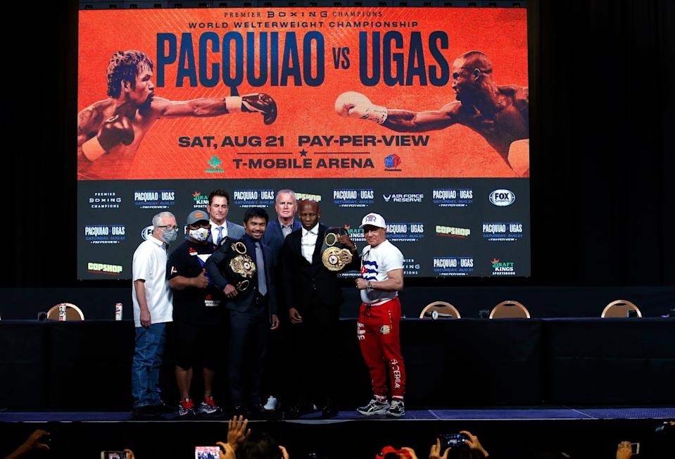 Manny Pacquiao, left, and WBA welterweight champion Yordenis Ugas pose with trainers and members of their teams at the MGM Grand Hotel & Casino on August 18.
