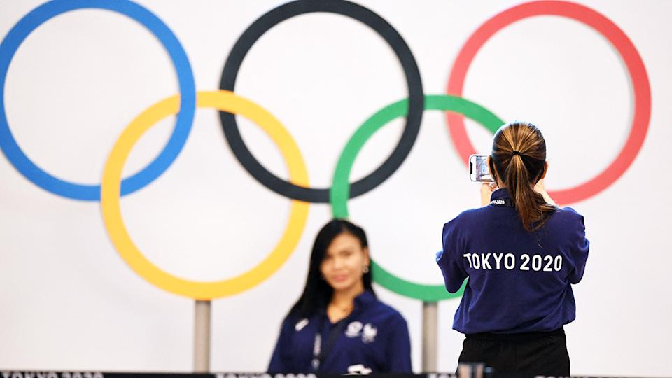 Airport operations staff, pictured here taking photos with the Olympic rings at Tokyo international airport.