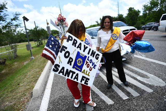 <p>Residents bring memorial items to Santa Fe High School on May 19, 2018 in Santa Fe, Texas. (Photo : Brendan Smialowski/AFP/Getty Images) </p>
