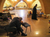 People and priests take refuge in an improvised bomb shelter in the separatist region of Nagorno-Karabakh, Friday, Oct. 30, 2020. The Azerbaijani army has closed in on a key town in the separatist territory of Nagorno-Karabakh following more than a month of intense fighting. (AP Photo)