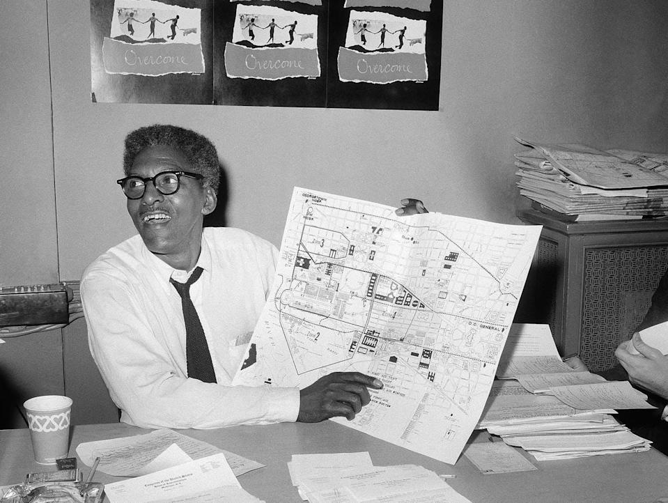 Black-and-white image of Rustin at a desk holding a big map and smiling, with papers all over this desk