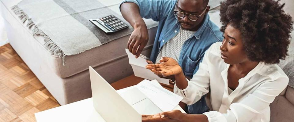 Desperate couple doing their accounts in the living room. Serious African American couple discussing paper documents, sitting together on couch at home, man and woman checking bills