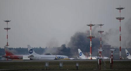 Smoke rises up from part of airfield where planes are parked at Vnukovo International Airport in Moscow