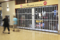 Vistors walk past a closed duty-free shop inside the Daniel K. Inouye International Airport Thursday, Oct. 15, 2020, in Honolulu. The COVID-19 pandemic has caused a devastating downturn on Hawaii's tourism-based economy. Many stores and restaurants inside the airport remain close due the the economic crisis. (AP Photo/Marco Garcia)