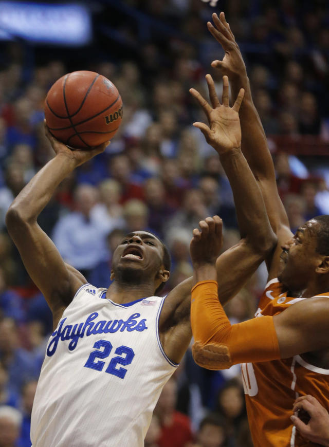 Kansas guard Andrew Wiggins (22) shoots while covered by Texas forward Jonathan Holmes, right, during the first half of an NCAA college basketball game in Lawrence, Kan., Saturday, Feb. 22, 2014. (AP Photo/Orlin Wagner)