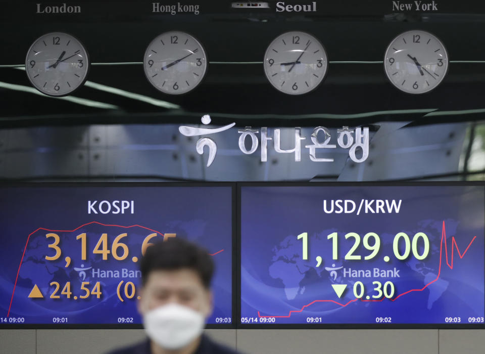 An employee of a bank walks by screens showing the Korea Composite Stock Price Index (KOSPI), left, and the foreign exchange rate between U.S. dollar and South Korean won at the foreign exchange dealing room in Seoul, South Korea, Friday, May 14, 2021. Asian shares rose Friday after Wall Street put the brakes on a three-day losing streak with a broad stock market rally powered by Big Tech companies and banks. (AP Photo/Lee Jin-man)