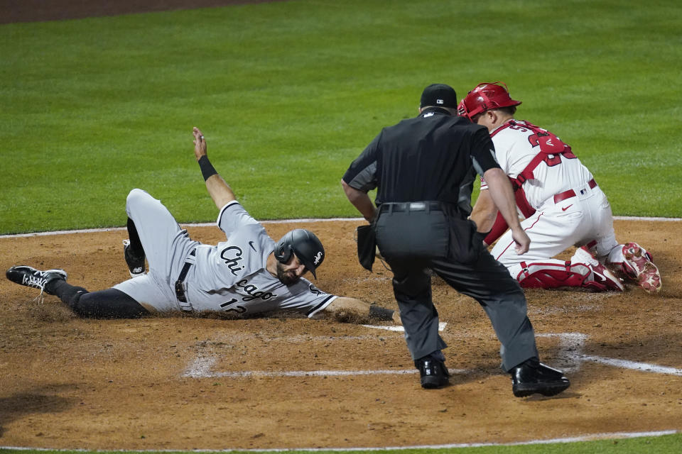 Chicago White Sox's Adam Eaton (12) avoids a tag attempt by Los Angeles Angels catcher Max Stassi (33) for a score during the fourth inning of an MLB baseball game Friday, April 2, 2021, in Anaheim, Calif. (AP Photo/Ashley Landis)