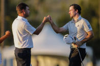 Nick Taylor, right, of Canada, bumps fists with Keith Mitchell as they finished the second round of the Sony Open golf tournament Friday, Jan. 15, 2021, at Waialae Country Club in Honolulu. (AP Photo/Jamm Aquino)