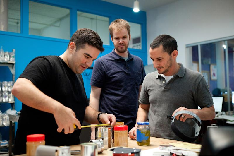 """In this image released by the Sundance Channel, Ben Kaufman, founder and CEO id Quirky, left, is shown with co-worker Gaz Brown, center, and product inventor Jon Corral as they work on a product called Apri, a type of can opener, in a scene from the original series, """"Quirky.""""  The series premieres Aug. 30, 2011 at 10 p.m. EST on Sundance Channel. (AP Photo/Sundance Channel, Christian Clothier)"""