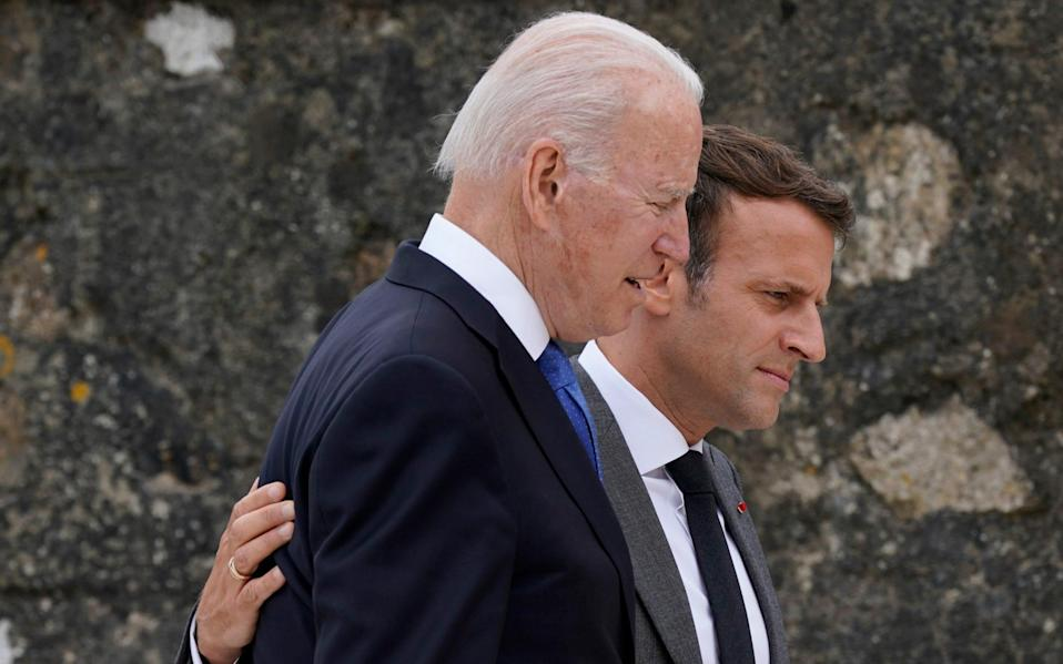 Emmanuel Macron puts his arm around Joe Biden as the leaders walk off after posing for the family photo - AP Pool