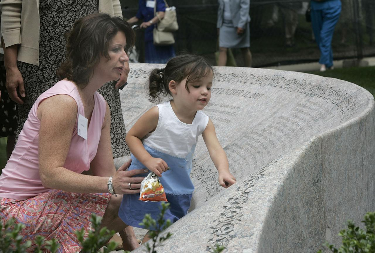 Leah Quigley, 2, touches the memorial in the Boston Public Garden in Boston, Monday, July 12, 2004, during a dedication ceremony of the memorial to the Massachusetts victims of the 9/11 terror attacks, as her mother Patti looks on. Patti Quigley's husband Patrick was killed in the Sept. 11, 2001, when Patti was a pregnant with Leah. (AP Photo/Chitose Suzuki)