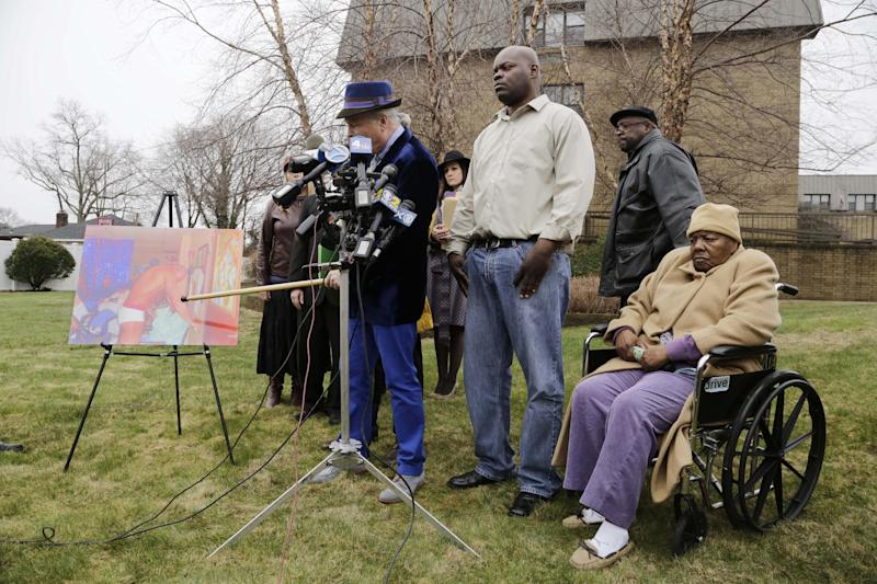 Bernice Youngblood, right, 85, a resident of the East Neck Nursing and Rehabilitation Center, listens as her attorney, John Ray, left, points to a photograph with his cane during a news conference on the lawn of the nursing home, Tuesday, April 8, 2014 in West Babylon, N.Y. The photograph reportedly shows a male exotic dancer performing for Youngblood and other patients at the facility. With Youngblood are her sons, Darrell, center, and Franklin, second right. (AP Photo/Mark Lennihan)