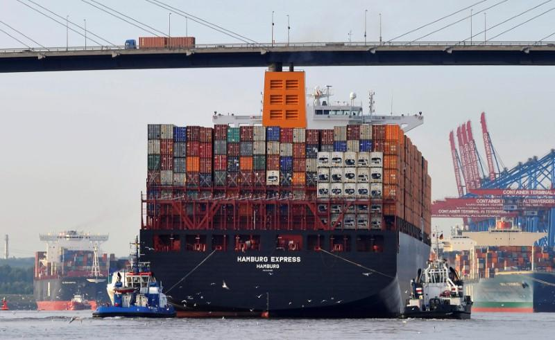 "Towboats tow the container ship ""Hamburg Express"" as it passes below the Koehlbrand bridge during its arrival near the Port of Hamburg"
