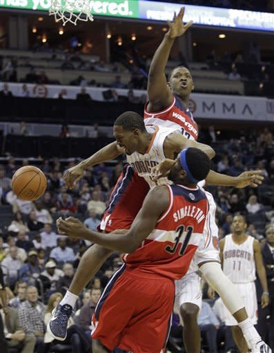 Charlotte Bobcats' Derrick Brown,center, is fouled as he drives between Washington Wizards' Kevin Seraphin, back, and Chris Singleton, front, during the first half of an NBA basketball game in Charlotte, N.C., Saturday, Jan. 28, 2012. (AP Photo/Chuck Burton)